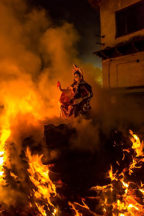 The figure of Holika burning a top a pyre during the Holika Dahan in Mathura on Purnima (full moon) the night before Holi; Mathura, Uttar Pradesh, India.