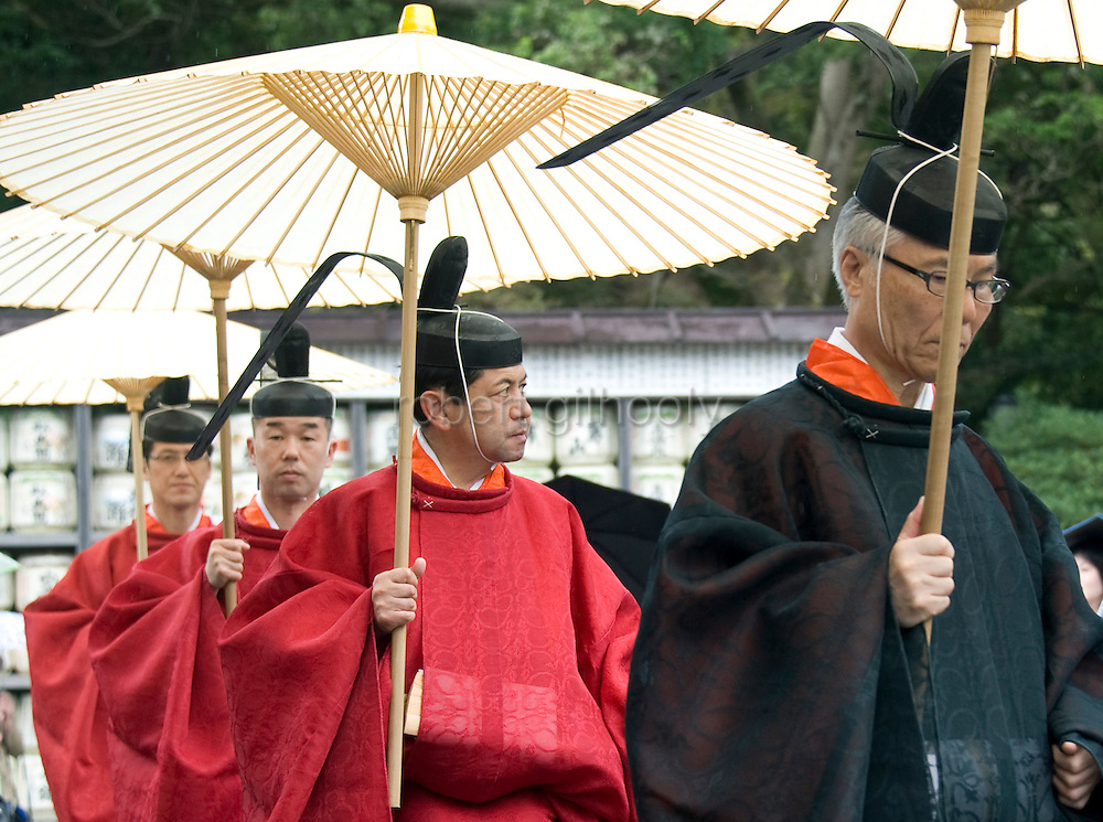 Shrine priests walk through the shrine grounds during the annual Reitaisai Grand Festival at Tsurugaoka Hachimangu Shrine in Kamakura, Japan on  14 Sept. 2012.  Sept 14 marks the first day of the 3-day Reitaisai festival, which starts early in the morning when shrine priests and officials perform a purification ritual in the ocean during a rite known as hamaorisai and limaxes with a display of yabusame horseback archery. Photographer: Robert Gilhooly