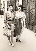 two fashionable dressed women walking on a sidewalk France 1957