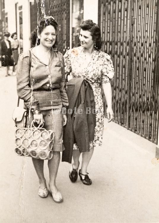 two fashionable dressed women walking on a sidewalk France 1957