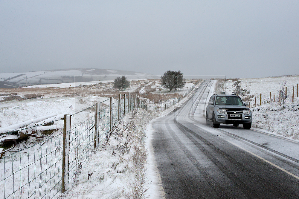 © Licensed to London News Pictures. 18/01/2019. Builth Wells, Powys, Wales, UK. A motorist negotiates the B4520 (Brecon Road) in a wintry landscape on the high moorland of the Mynydd Epynt range (approximately 400 metres above sea-level) near Builth Wells in Powys, Wales, UK Heavy snow hits Powys Wales, UK. credit: Graham M. Lawrence/LNP