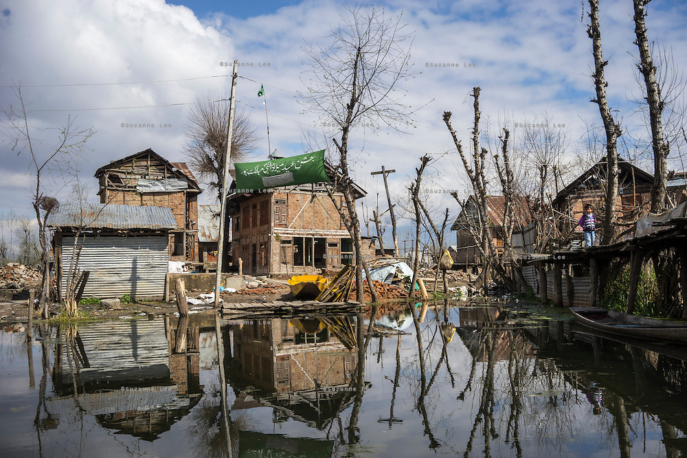 A child stands on a wooden bridge amidst destroyed properties on the Dal Lake, Srinagar, Jammu and Kashmir, India, on 25th March 2015. Nearly 2500 villagers including Srinagar, the capital of the state of Jammu and Kashmir, was devastated by severe floods and landslides in September 2014 the worst in 60 years, displacing millions of people, many of them children. Photo by Suzanne Lee for Save the Children