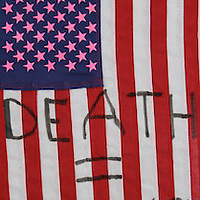 There is a sign Silence = Death. I say this was Regan's flag during the AIDS epidemic.