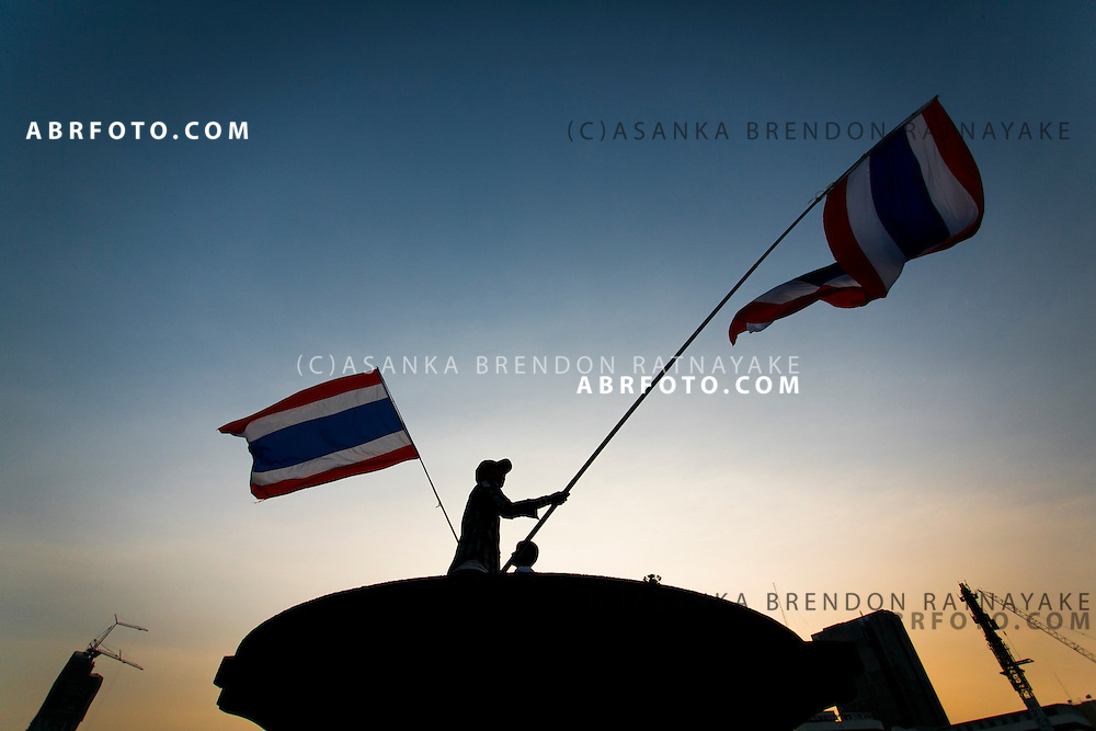 Anti-Thai government protestors (PDRC) wave the Thai Flag at Victory Monument, one of the many protest sites spread throughout Bangkok.