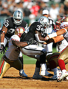 OAKLAND, CA - AUGUST 20:  Running back LaMont Jordan #34 of the Oakland Raiders gets gang tackled on a running play by the San Francisco 49ers defense at McAfee Coliseum on August 20, 2006 in Oakland, California. The Raiders defeated the Niners 23-7. ©Paul Anthony Spinelli *** Local Caption *** LaMont Jordan