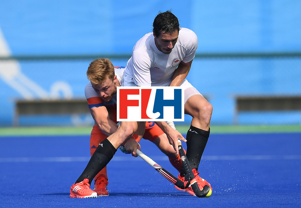 Canada's Matthew Guest (R) vies for the ball with Netherland's Sander Baart during the men's field hockey Netherlands vs Canada match of the Rio 2016 Olympics Games at the Olympic Hockey Centre in Rio de Janeiro on August, 9 2016. / AFP / MANAN VATSYAYANA        (Photo credit should read MANAN VATSYAYANA/AFP/Getty Images)