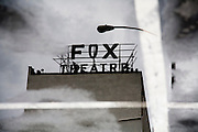 Historic Fox Fullerton theater sign reflected in puddle of Angelo and Vinci's parking lot.