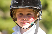 A young equestrian rider with her face painted smiles at the camera during Cobble Hill's fall festival.  Cobble Hill, Vancouver Island, British Columbia, Canada.