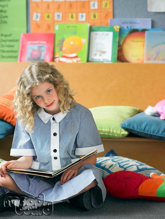 Elementary schoolgirl reading book sitting on floor in classroom portrait