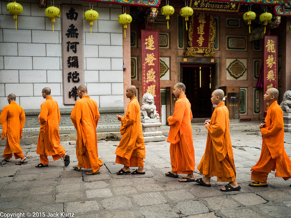 12 OCTOBER 2015 - BANGKOK, THAILAND:  Mahayana Buddhist novices walk across the temple grounds at Wat Mangkon Kamlawat, a large Chinese temple in Bangkok, on the first day of the Vegetarian Festival in Bangkok's Chinatown. The Vegetarian Festival is celebrated throughout Thailand. It is the Thai version of the The Nine Emperor Gods Festival, a nine-day Taoist celebration beginning on the eve of 9th lunar month of the Chinese calendar. During a period of nine days, those who are participating in the festival dress all in white and abstain from eating meat, poultry, seafood, and dairy products. Vendors and proprietors of restaurants indicate that vegetarian food is for sale by putting a yellow flag out with Thai characters for meatless written on it in red.     PHOTO BY JACK KURTZ