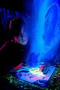 Young girl with glowing Ouija board visited by ghostly apparition.Black light