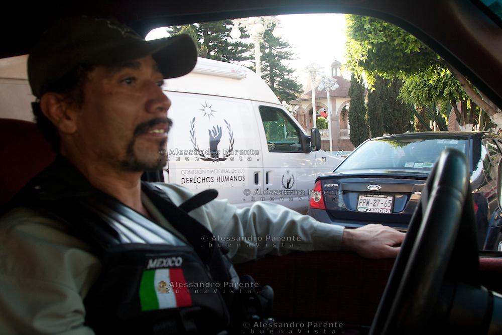 """lo """"zio Sam"""" pattuglia la città. Sullo sfondo un furgone dei diritti umani. L'autodifesa si lamenta della loro apparizione solo ora e nei luoghi con più attenzione mediatica."""
