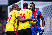 Watford (16) Abdoulaye Doucouré, Watford (27) Christian Kabasele, Wilfried Zaha (11) of Crystal Palace  during the Premier League match between Watford and Crystal Palace at Vicarage Road, Watford, England on 21 April 2018. Picture by Sebastian Frej.
