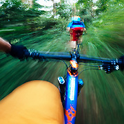 Jay Goodrich and Andrew Whiteford ride single track through the jungle near Chiang Mai, Thailand.