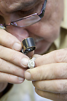 Cropped image of a mature worker looking through loupe at ring