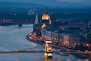 An aerial view of Budapest from Gellert-hegy including the Chain Bridge, Parliament and the Danube River at dusk.  Hungary