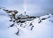 Snow coasts the ledges at Portland Head Light as the beam of the lighthouse shines through the storm.