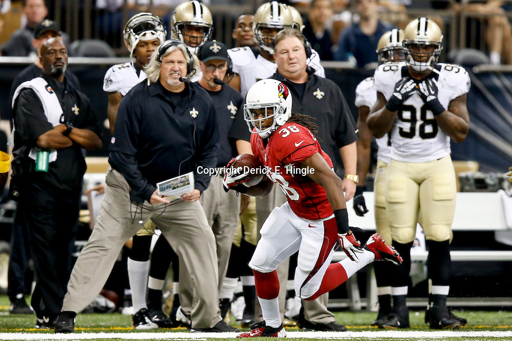 Sep 22, 2013; New Orleans, LA, USA; Arizona Cardinals running back Andre Ellington (38) runs as New Orleans Saints defensive coordinator looks on from the sideline during a game at Mercedes-Benz Superdome. The Saints defeated the Cardinals 31-7. Mandatory Credit: Derick E. Hingle-USA TODAY Sports