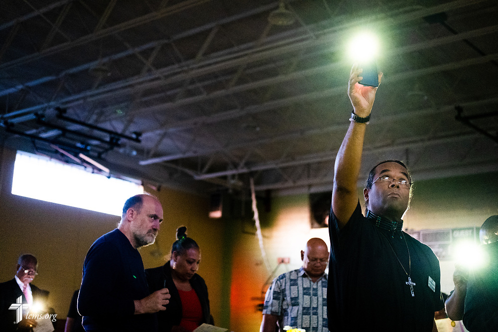 Dr. Victor Singingeagle lifts his mobile phone flashlight during a vigil for the faithfully departed during the Legacy/Candlelight service on Friday, April 27, 2018, in the Lehman Center at Concordia College Alabama in Selma, Ala. LCMS Communications/Erik M. Lunsford