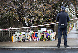 © Licensed to London News Pictures. 02/04/2018. London, UK. A police officer stands in front of tributes left near Ellerton Road in Wandsworth, south west London, where 20 year old Devoy Stapleton was stabbed to death at 1am on Sunday 1st April - the 31st fatal stabbing this year in the capital. It is being reported that London's murder rate has overtaken New York's.   Photo credit: Peter Macdiarmid/LNP