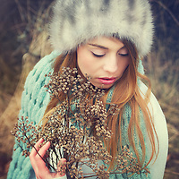 Young women standing in the nature and wearing a grey/blue dress and a fur cap.an holding dried flowers in her hands