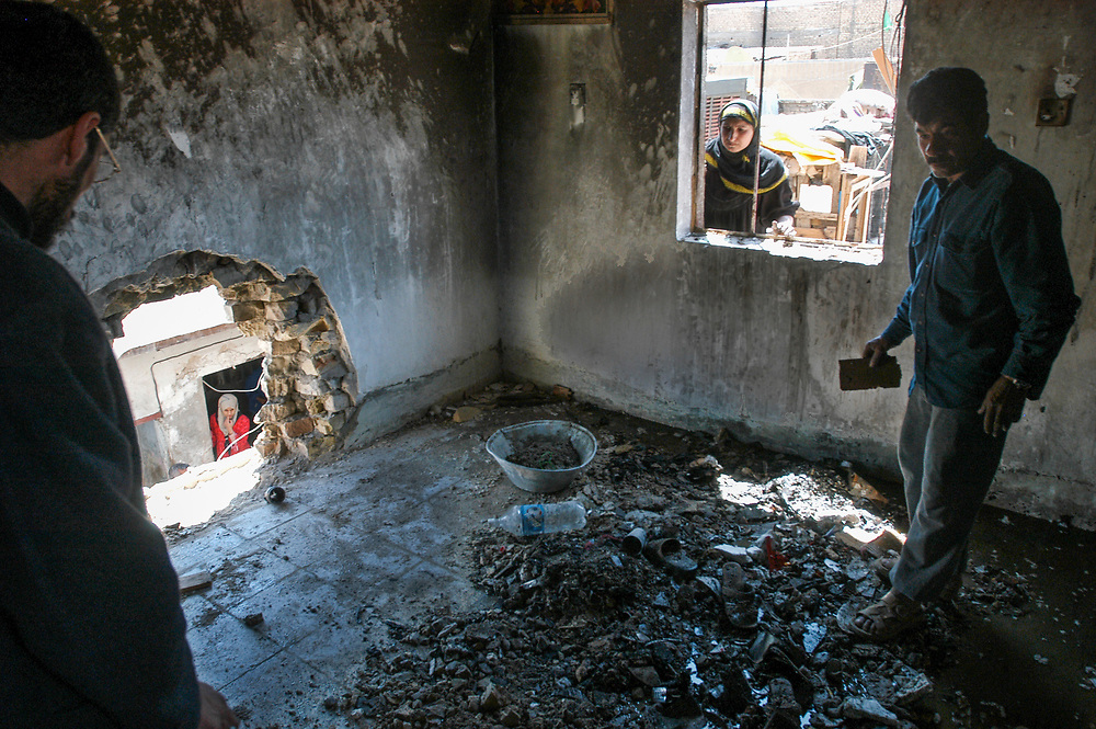 Residents of the poor Shia neighborhood of Sadr City clean out a house that was targeted by US forces during nightly battles with supporters of radical Shia cleric Moqtada al-Sadr. A man and wife and their one year old baby were sleeping in the room at the time.<br /> Baghdad, Iraq. 06/04/2004.