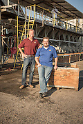 Keith and Matt Jura stand in front of the fig sorting machine at the Nutra Fig plant in Fresno, California.