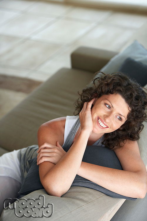 Woman sitting on couch in living room smiling elevated view