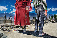A monk and a boy standing on what used to be a three story building. It was reduced to a rubble after flash floods hit Leh following a cloudburst on 6th Aug. 2010.