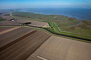 Nederland, Groningen, Oldambt, 08-09-2009; Dollard en Reiderwolderpolder, de polder is onstaan door landaanwinning. Op het tweede plan de Carel Coenraadpolder. Het kanaal is het boezemkanaal, dit loost op de Nieuwe Buitengeul van Reiderland, in de Dollard. Aan de horizon windmolens langs de Duitse kust bij Emden. Aan de andere kant van de zeedijk de kwelders van de Dollard..Estuarium of the Dollard and Reiderwolderpolder, created  by land reclamation. At the horizon windmills in Germany (Emden), at the other side of the dike the salt marshes of the wad / the Wadden Sea..luchtfoto (toeslag); aerial photo (additional fee required); .foto/photo Siebe Swart