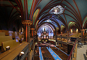 View of the nave and ceiling looking towards the main altar carved by Charles Daudelin, from the upper balcony in the Basilique Notre-Dame de Montreal, built in 1823 in Gothic Revival style by James O'Donnell, in Montreal, Quebec, Canada. The rib vaulted ceiling is painted blue with gold stars. It is listed as a National Historic Site of Canada. Picture by Manuel Cohen