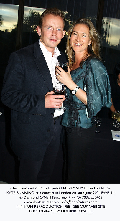Chief Executive of Pizza Express HARVEY SMYTH and his fiancé KATE BUNNING, at a concert in London on 30th June 2004.PWR 14