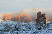 The golden light of sunrise blankets Elephant Butte, covered in fresh snow, in Arches National Park, Utah.