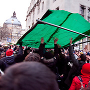 Thousands of students and protesters took to the streets of London on the day of the vote on rise in tuition fees in the House of Commons. Fences from arund the square is pulled up and thrown at police.