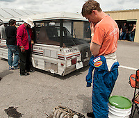 Gordy Sheer feels the pain of  Speedy Cop and the Gang of Outlaws Team as they desperately tried to put their Viking Camper back out on the track Sunday afternoon during the 24 Hours of Lemons at New Hampshire Motor Speedway in Loudon.  (Karen Bobotas/for the Concord Monitor)