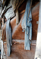 Two pairs of farmer's overalls decay as they hang on the wall of an abandoned home collapasing on itself in Monowi, Nebraska April 28, 2011. At its peak in the 1930's the town had 150 residents but after the railroad left it began to decline. Now down to a population of just one, Monowi is the only incorporated town, village or city in the United States with just a single resident.  REUTERS/Rick Wilking (UNITED STATES)