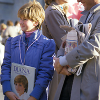 A young girl awaits the arrival of Diana Princess of Wales displaying both a hairstyle and a book showing her devotion to the British Royal.
