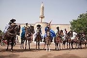 Participants in the FECHIBA horse festival line up in front of a mosque in Barani, Burkina Faso, West Africa