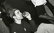 Man drinking at the first outdoor rave up North, The Gio Goi Joy Rave run by Anthony and Chris Donnelly, Ashworth Valley, Rochdale, 5th August 1989.