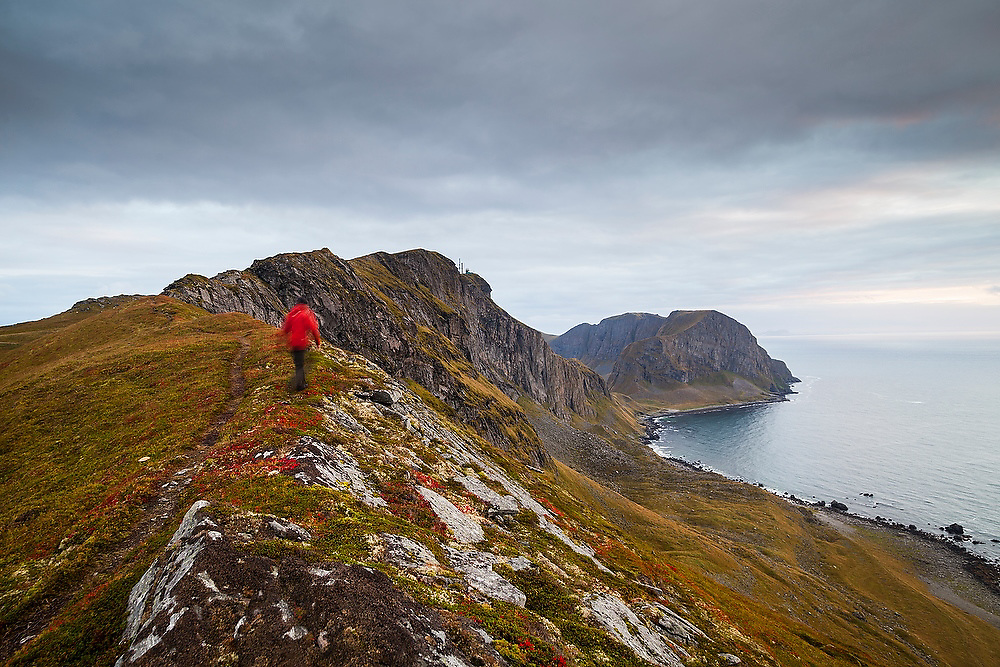 Ethan Welty hikes the crest of Vaeroy Island at sunset, Lofoten Islands, Norway. The North Atlantic Treaty Organization (NATO) naval military radar is visible on a distant ridge.