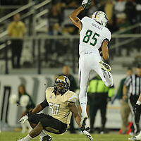 South Florida Bulls wide receiver Ruben Gonzalez (85) leaps over UCF Knights linebacker Troy Gray (57) during an NCAA football game between the South Florida Bulls and the 17th ranked University of Central Florida Knights at Bright House Networks Stadium on Friday, November 29, 2013 in Orlando, Florida. (AP Photo/Alex Menendez)