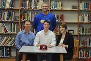 Oxford High baseball player William Elliott (center), with his parents Allen (left) and Kathryn Elliott (right), and head coach Chris Baughman, signs to play baseball at Alabama, in Oxford, Miss. on Wednesday, November 14, 2012.