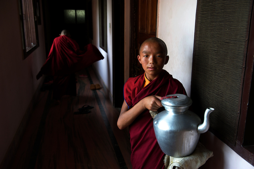 A novice monk serves tea to the student novice monks, studying traditional buddhist scripts in the very location where Siddartha himself acquired most of his learning, at Sarnath, outside Varanasi.