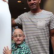 "Blake, a young kidney recipient, poses with ASP World Champion Kelly Slater at the ""Taste of Brevard"" dinner and auction on day two of the 28th annual National Kidney Foundation, Rich Salick Pro/Am surf festival on Friday, September 1, 2013 in Cocoa Beach, Florida. This event raises thousands of dollars for people with kidney disease and also benefits the services of the NKF of Florida. (AP Photo/Alex Menendez)"