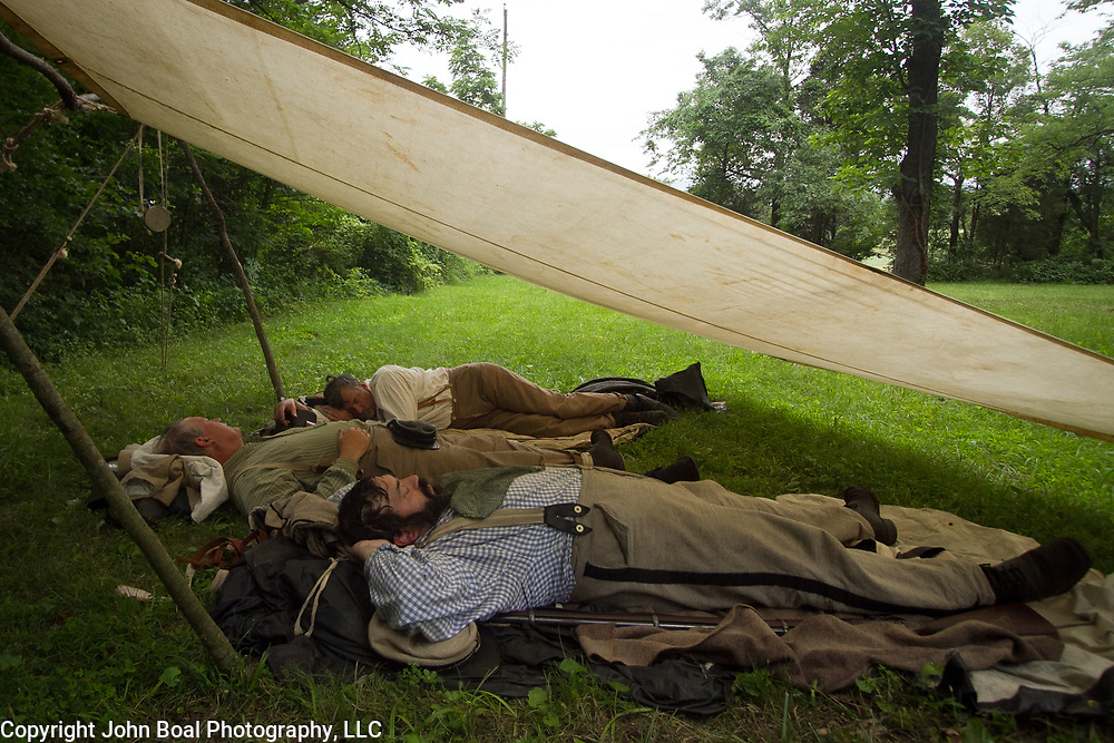 From front to back, Matt Duvall, of Millersville, Maryland, Russell Dashiell, of Salisbury, Maryland, and Ray Swearingen, of Ocean Pines, Maryland, all try to get a quick nap in before educating visitors as a living historian at a Confederate encampment, during the Sesquicentennial Anniversary of the Battle of Gettysburg, Pennsylvania on Wednesday, July 3, 2013.  The Battle of Gettysburg lasted from July 1-3, 1863 resulting in over 50,000 soldiers killed, wounded or missing.  John Boal Photography
