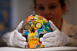 "© Licensed to London News Pictures. 14/09/2018. LONDON, UK. A technician inspects ""The Hours Spin Skull"", 2009, by Damien Hirst (Est. GBP3,000-4,000) at a preview of the ""Yellow Ball: The Frank and Lorna Dunphy Collection"" sale at Sotheby's in New Bond Street.  Frank Dunphy was Damien Hirst's former business manager and mentor.  Over 200 works will be auctioned by Sotheby's on 20 September 2018.  Photo credit: Stephen Chung/LNP"
