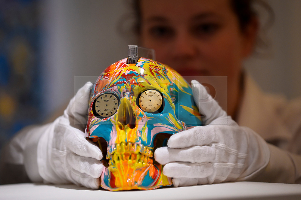 """© Licensed to London News Pictures. 14/09/2018. LONDON, UK. A technician inspects """"The Hours Spin Skull"""", 2009, by Damien Hirst (Est. GBP3,000-4,000) at a preview of the """"Yellow Ball: The Frank and Lorna Dunphy Collection"""" sale at Sotheby's in New Bond Street.  Frank Dunphy was Damien Hirst's former business manager and mentor.  Over 200 works will be auctioned by Sotheby's on 20 September 2018.  Photo credit: Stephen Chung/LNP"""