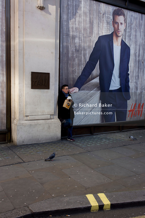 Man eats a sandwich beneath a poster for retailer H&M on Oxford Street.