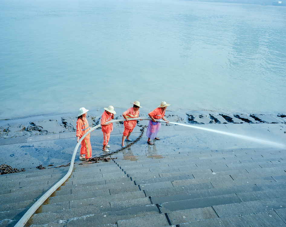 Workers hose off the steps at Chaotianmen dock.