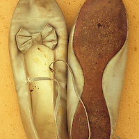 Pair of ballet or dancing shoes once white but now used and grubby sitting one face down on antique paper